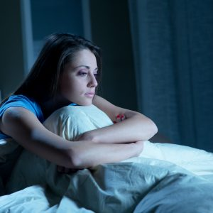 young woman sitting up in bed with insomnia