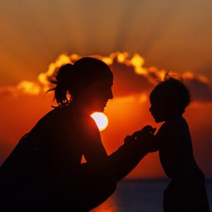 Happy mother and joyful son sunset silhouette.