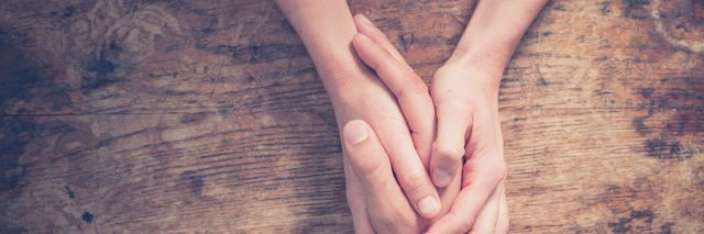 a person holding their friend's hand in support