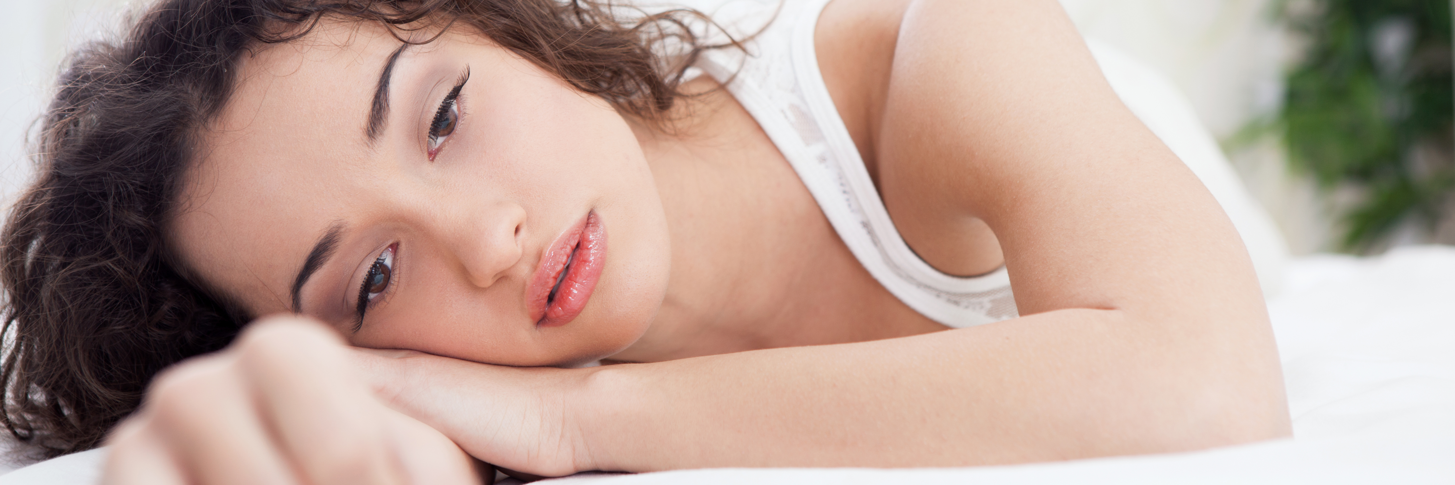 young woman brown hair lying in bed unhappy