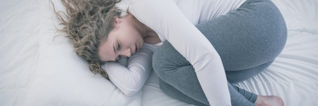 young woman curled up on bed looking depressed