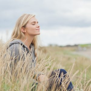 a woman sitting in field of grass