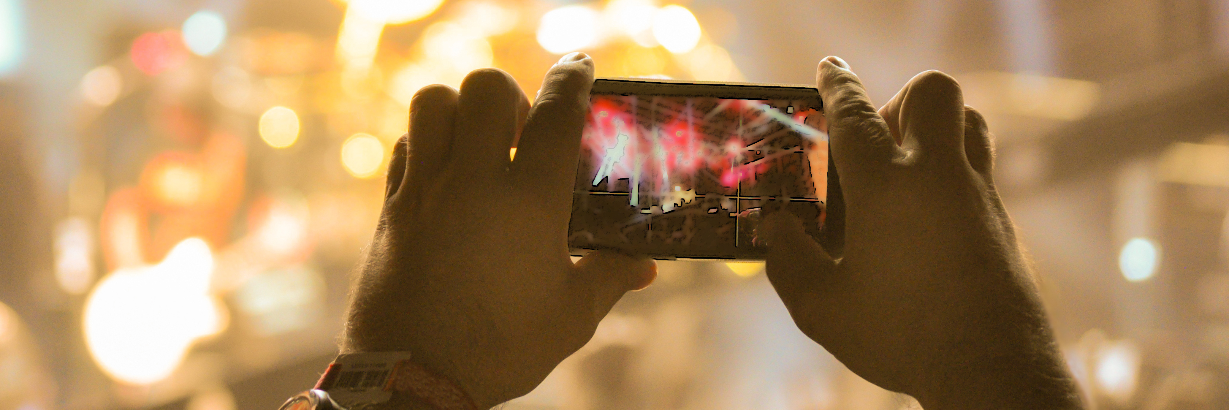 Someone taking a photo at a concert on their cell phone.