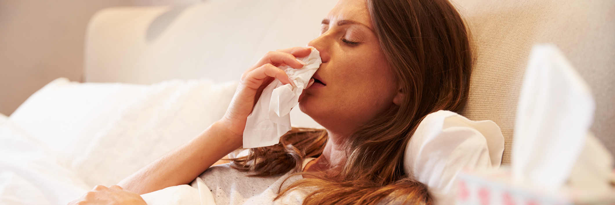 woman in bed blowing her nose