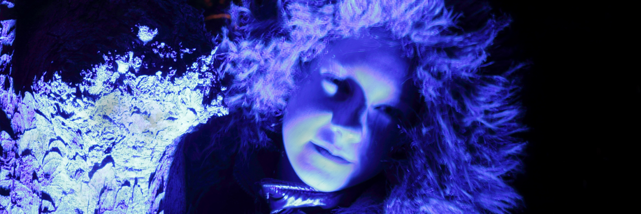 Focus on blue illuminated treebark, a girl with furry hood next to it