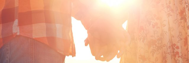 A couple holding hands, sunshine flowing through their arms.