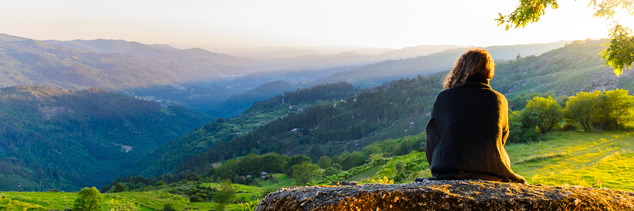 scenic view at Peneda-Geres National Park, northern Portugal of woman watching sunset over valley