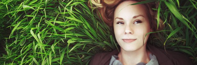 young woman lying in summer grass