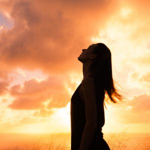woman looking at the sky at sunset