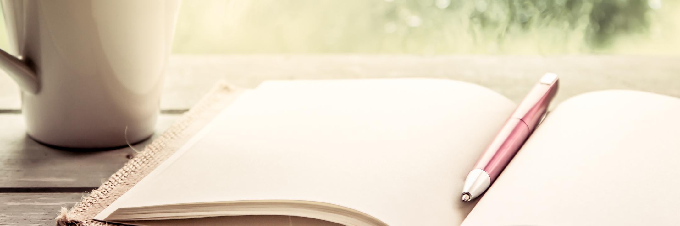 pen on an open notebook sitting next to a mug on a windowsill