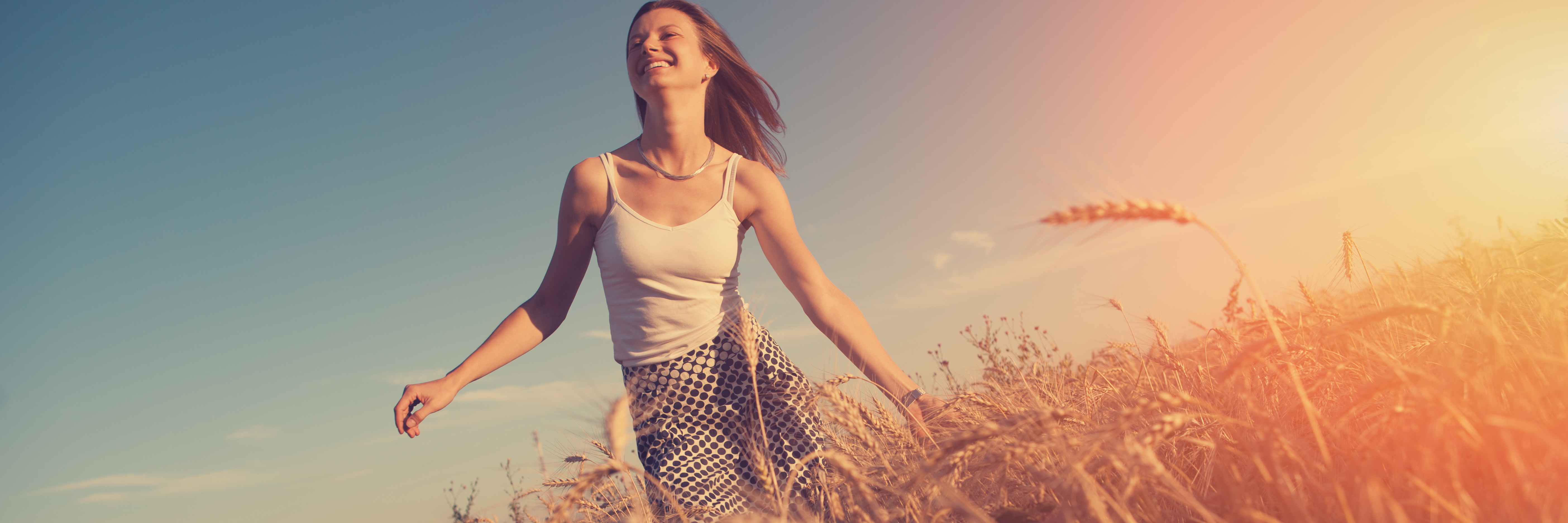 young woman running through field at sunset in summer wearing short sleeved top