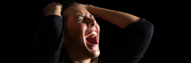 Depressed woman crying and shouting desperately isolated in a black background