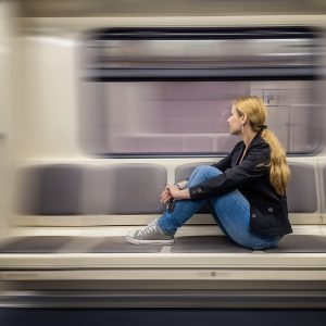 A blonde woman sitting in subway train and looking at window.