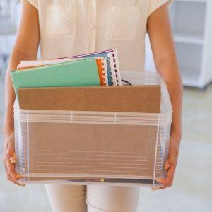 woman holding a box of her things after being let go from a job