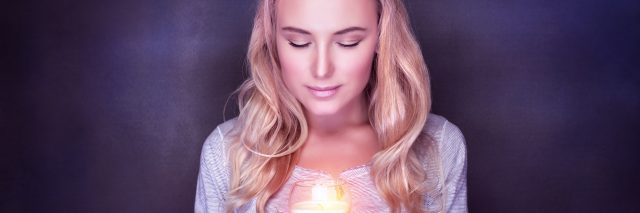 A woman in front of a dark background hodls a burning candle.