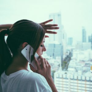 woman on phone standing at window looking out at gray sky