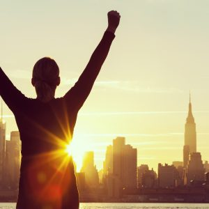 woman with her arms raised in success by the new york skyline at sunrise