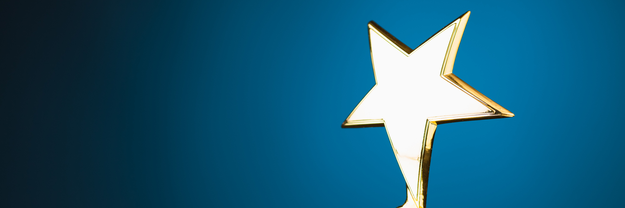 shiny gold star trophy against blue background with copy-space