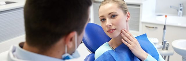 young blonde woman at male dentist pointing to side of face