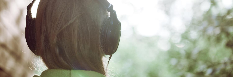 Woman wearing headphones, outdoors facing trees