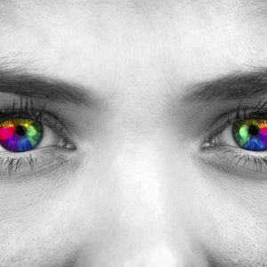 black and white photo of a woman's face with her eyes colored rainbow