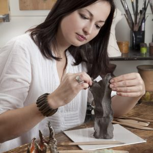 Woman shaping clay sculpture.