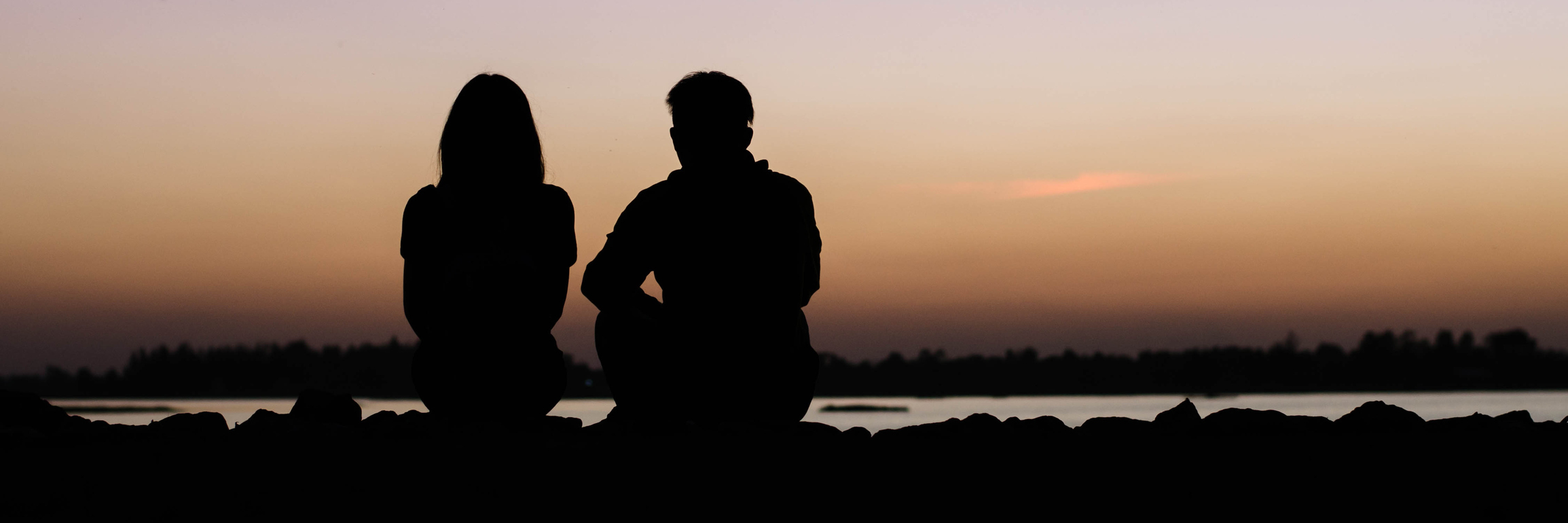 silhouette of man and woman against sunset