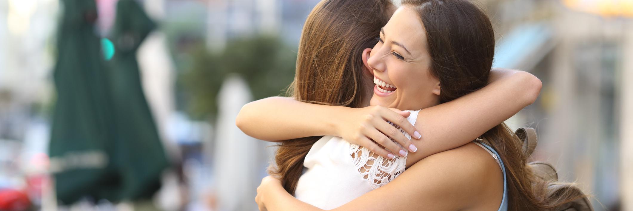 Two friends hugging outside.