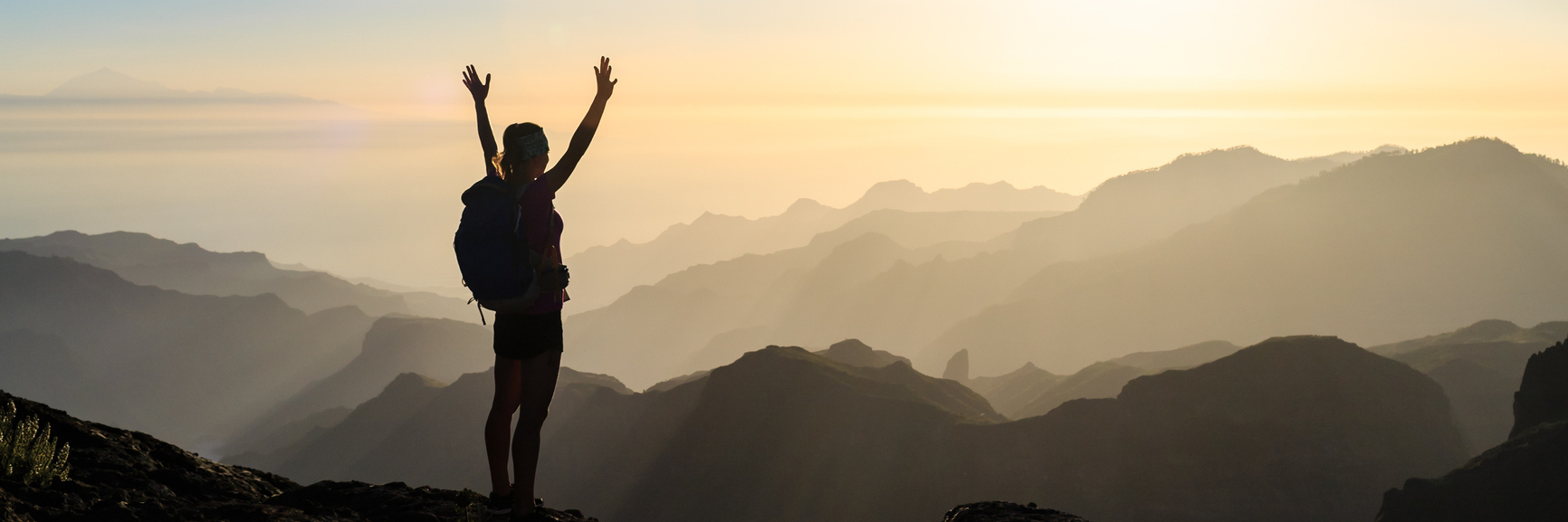 woman standing on the top of a mountain at sunrise with her arms outstretched