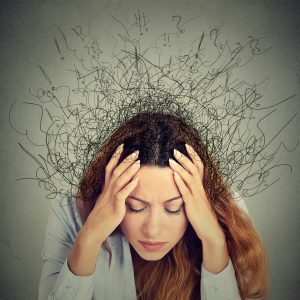 close up photo of woman with hands on head with lines coming from head in messy way