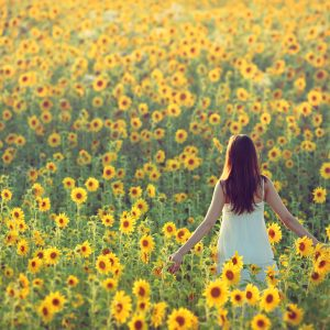 woman standing in a field of sunflowers