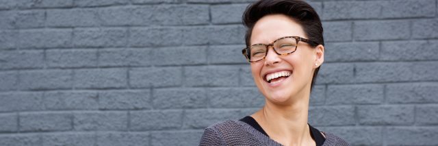 woman with glasses laughing in front of a gray wall