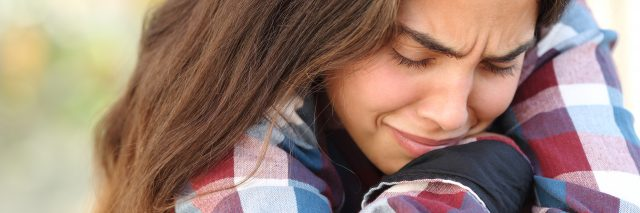 teenage girl in checkered shirt sitting outdoors crying hugging knees
