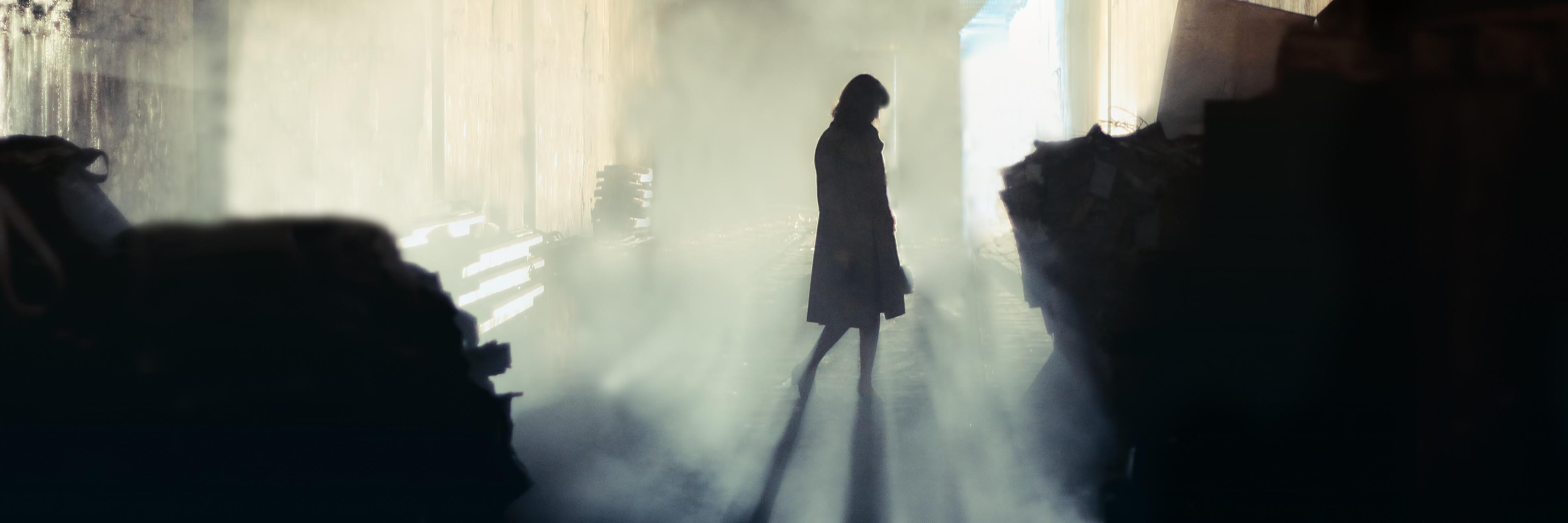 lone woman standing in misty tunnel