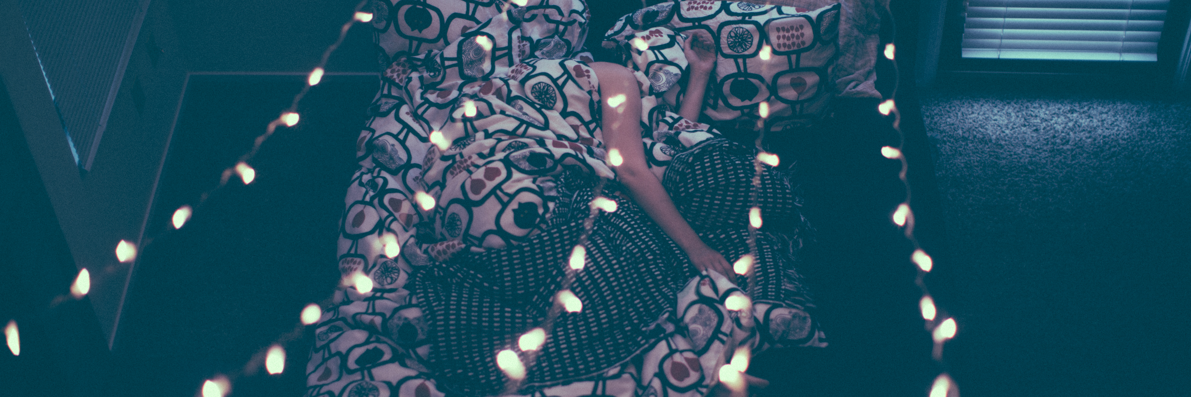 overhead photo of woman lying in bed with lights above her covered with duvet