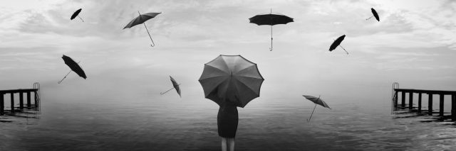 A woman stands at the end of the pier with umbrellas flying around her in the air.