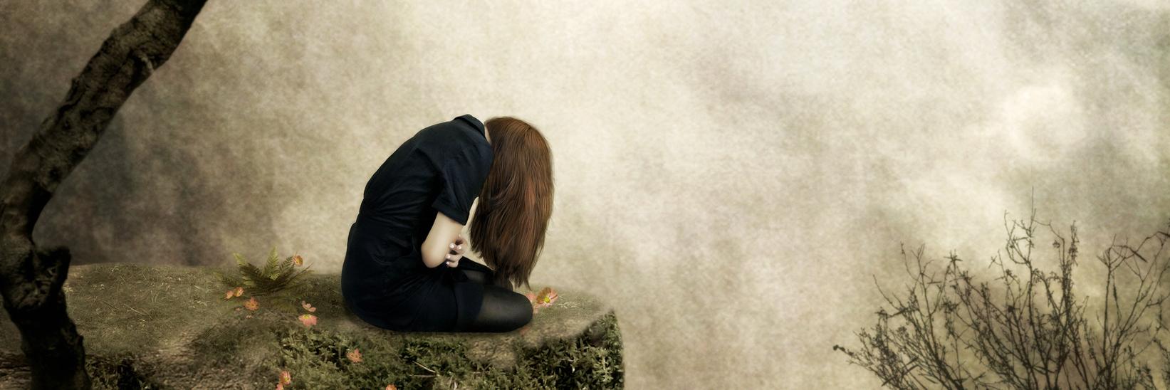 Sad girl sitting alone on a ciff.