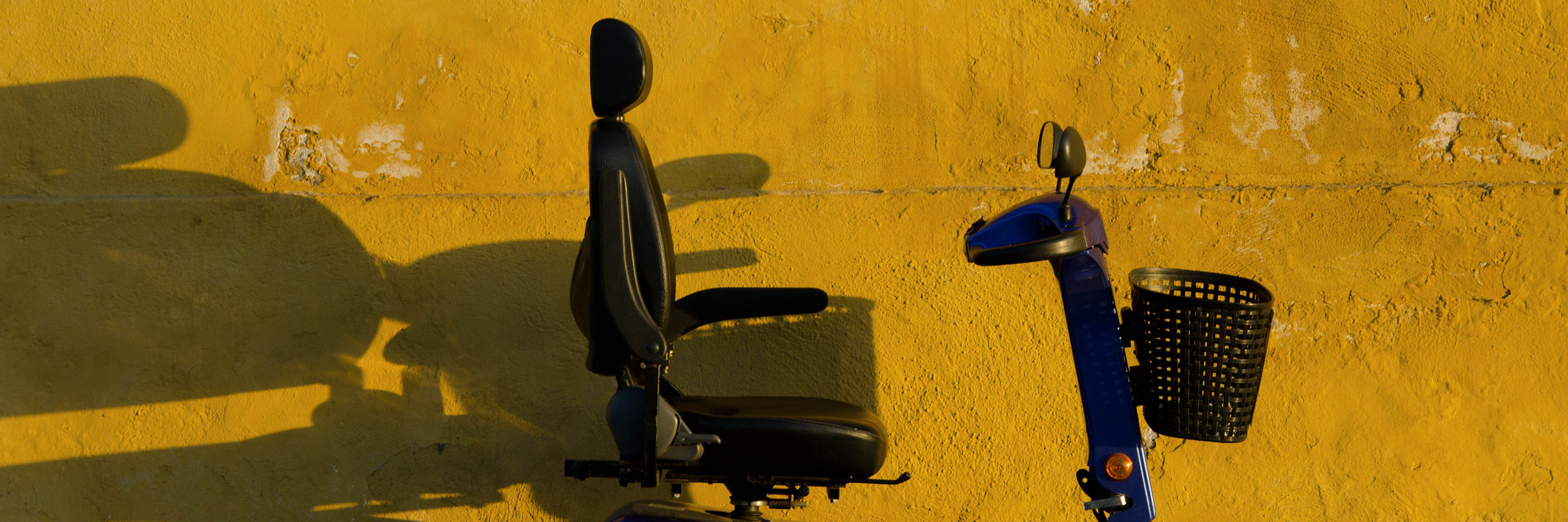 Blue scooter against yellow wall.