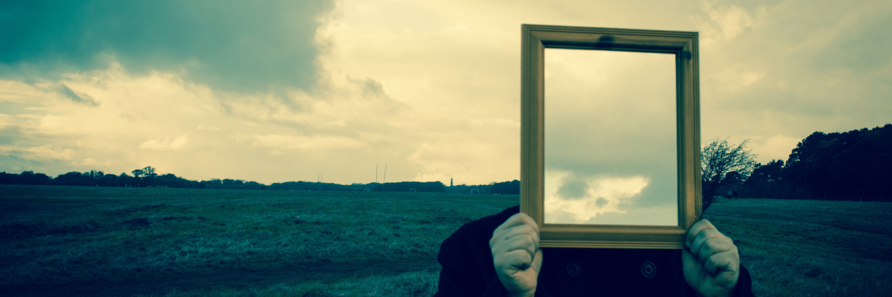 a man in a field holding a mirror over his face reflecting back clouds