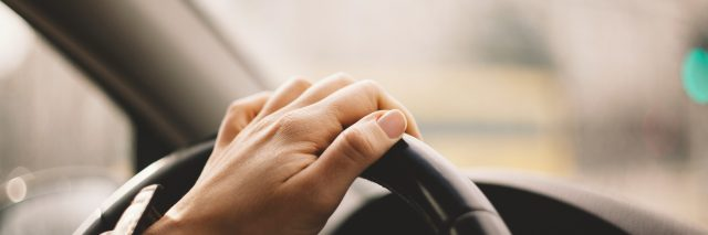 Close-up of a woman's hand driving a car.