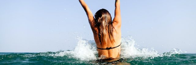 A woman throwing her hands up standing in the ocean