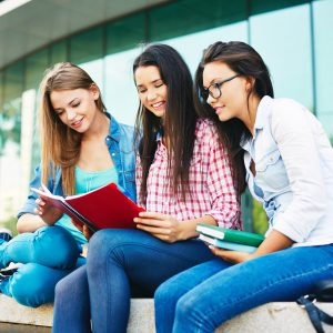 Modern teen girl reading in urban environment