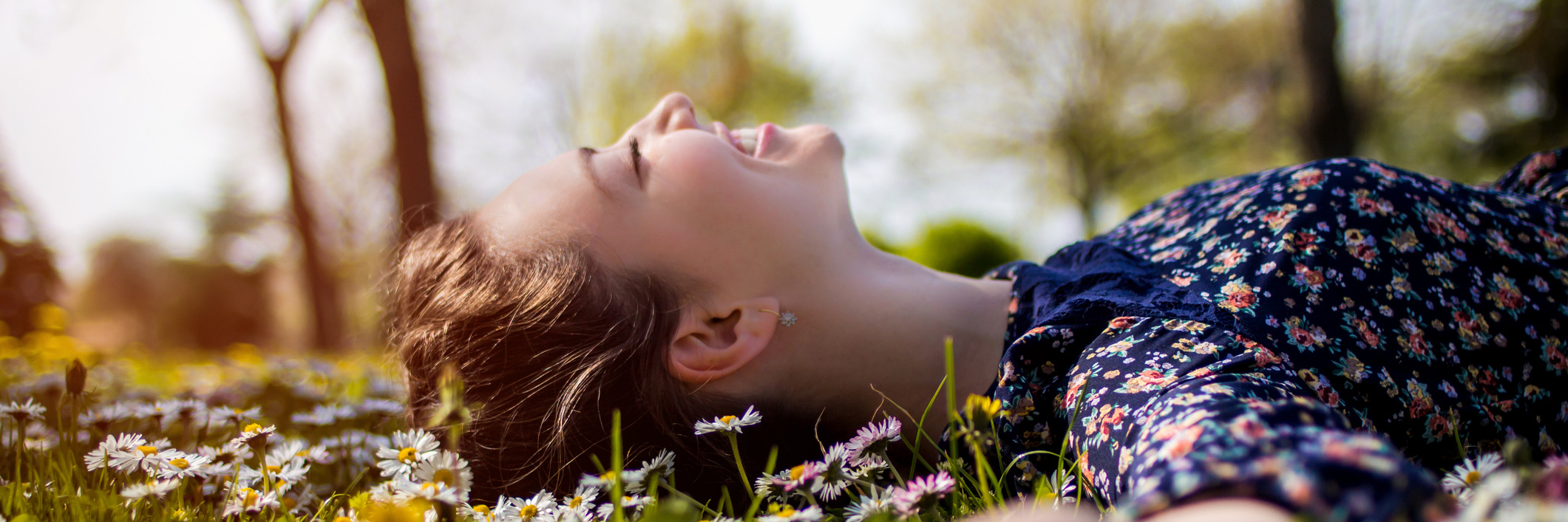 woman lying in field of flowers and smiling
