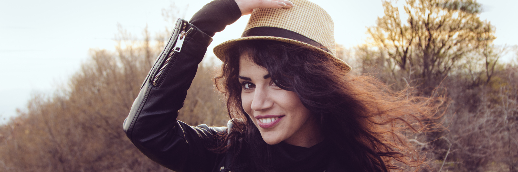 A brunette woman wearing a hat outdoors.