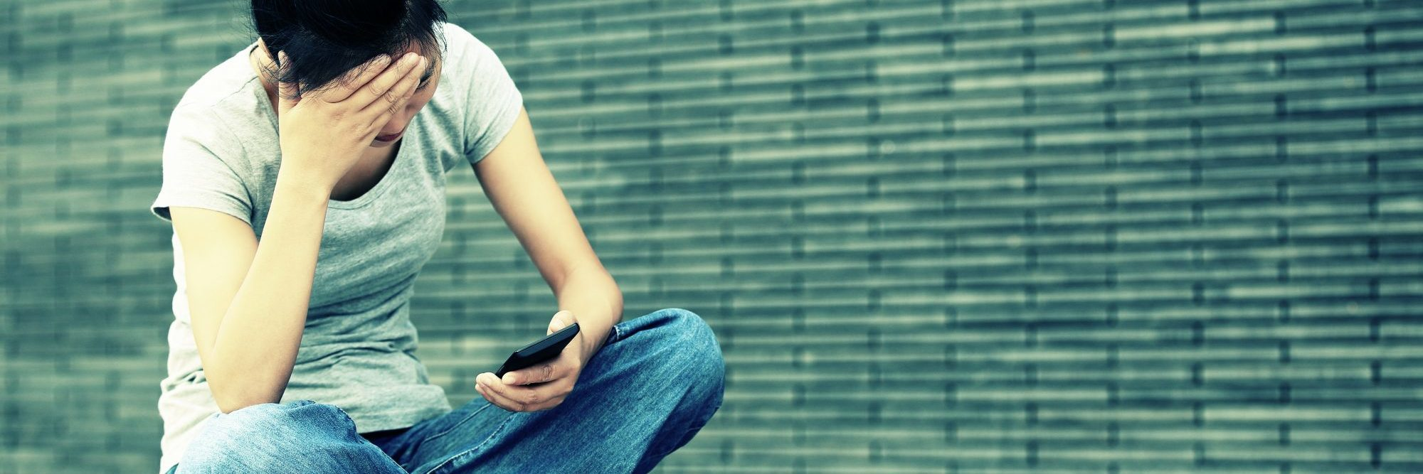 young asian woman sitting cross legged in city with smartphone