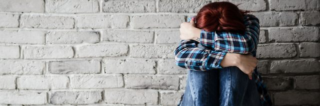 young crying depressed woman with head buried in arms sitting against a brick wall