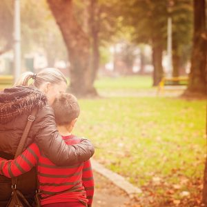 woman hugging son and walking in park