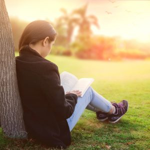 woman sitting outside leaning against a tree and reading