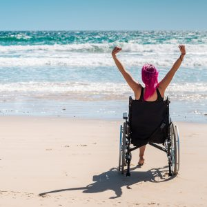 Disabled woman in a wheelchair on the beach.