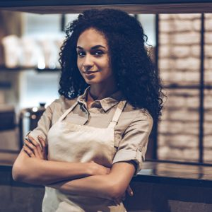 young confident proud african american black woman crossed arms leaning against counter